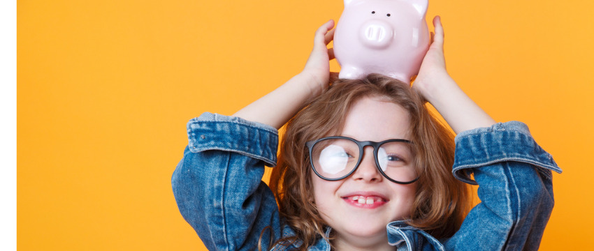 Little girl holding a piggy bank on her head